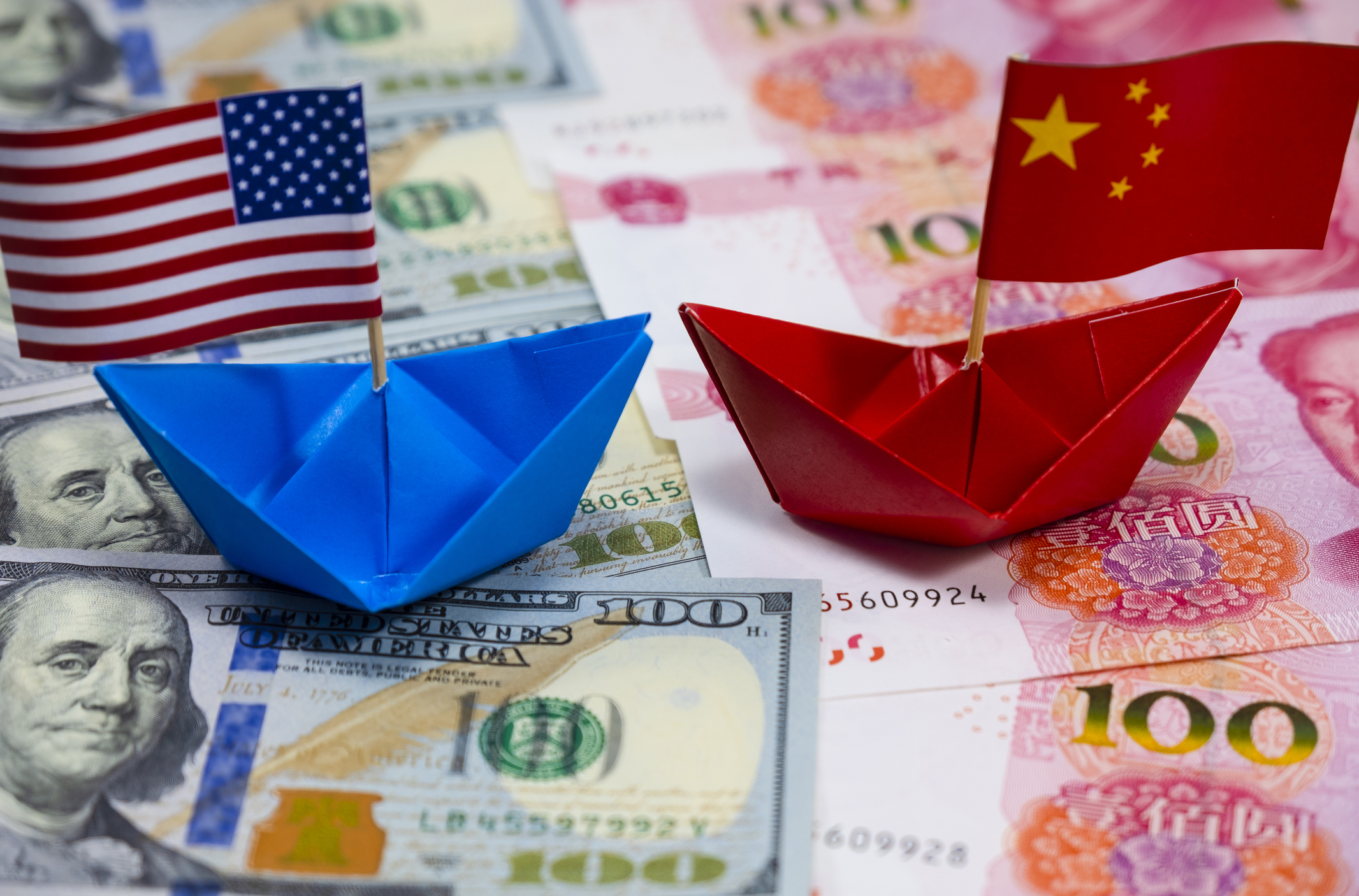 United States Paper Ship vs. Chinese Paper Ship floating on country currencies