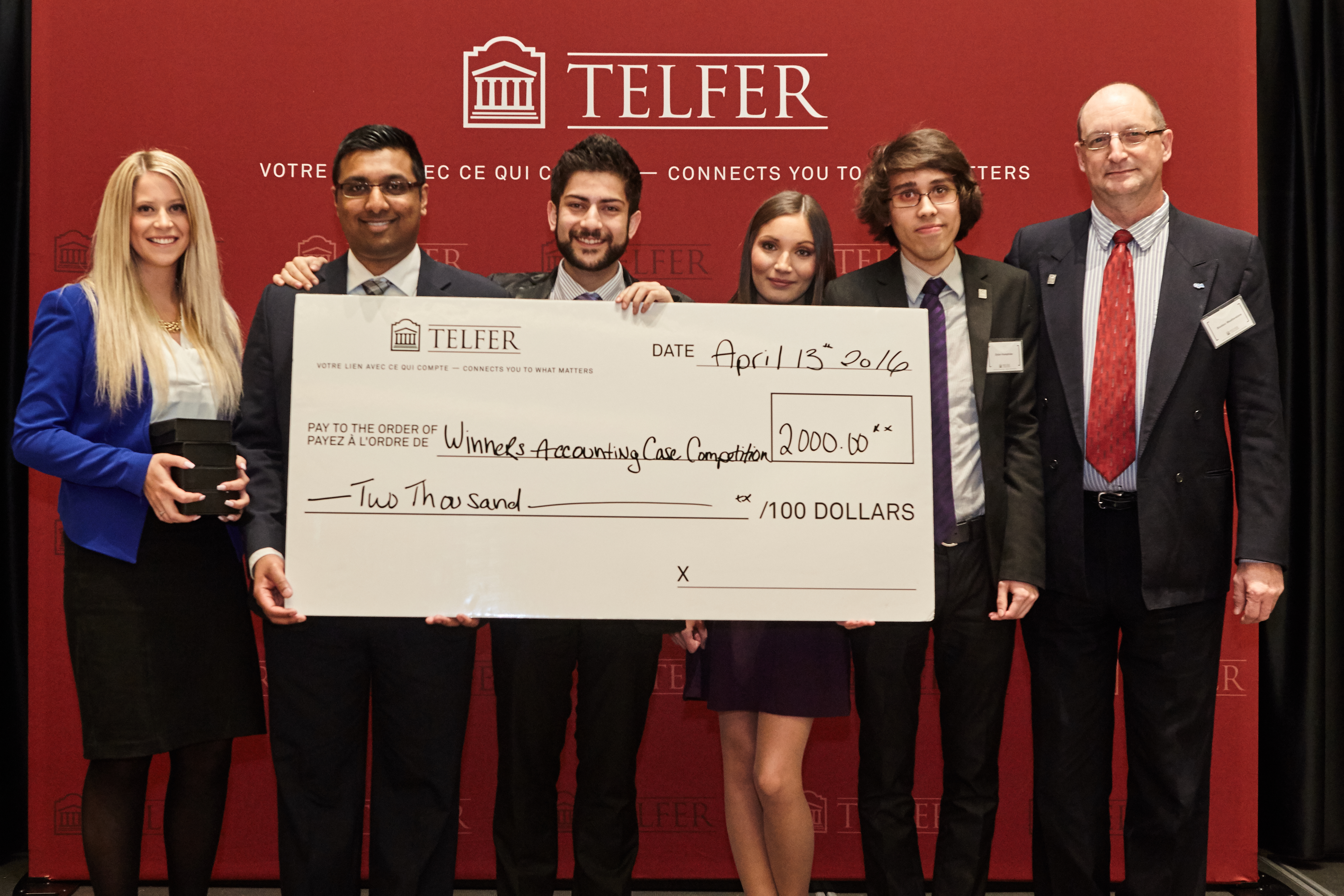 winners of the accounting capstone standing in front of a branded backdrop with their prize cheque.