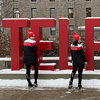 three students smiling in front of the telfer sign