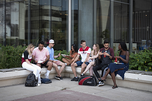 Telfer students sitting and studying in front of the large windows outside of the Faculty of Social Science (FSS)