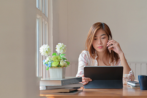 female college student working from home with cellphone and tablet