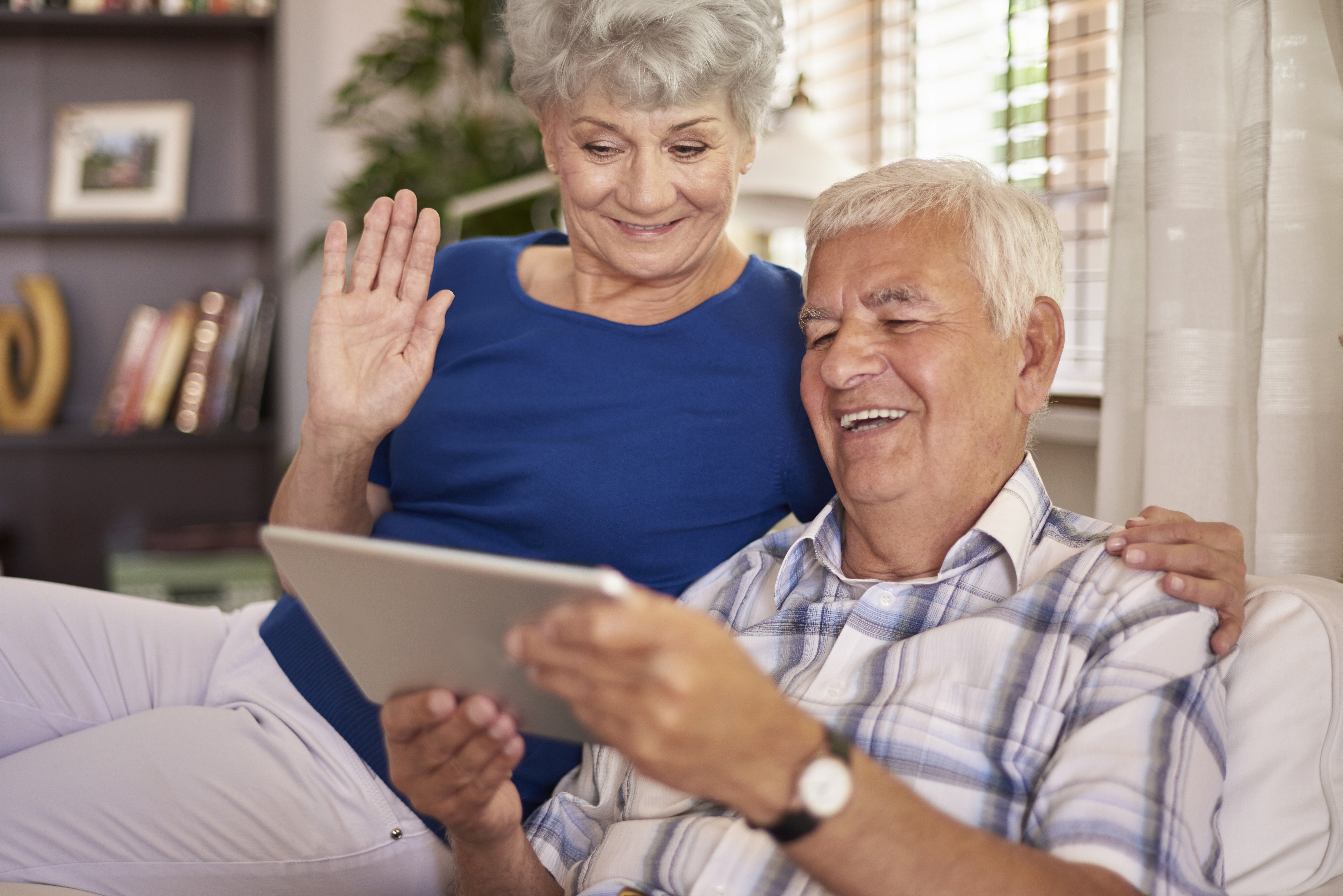 cheerful senior couple looking at an electronic tablet