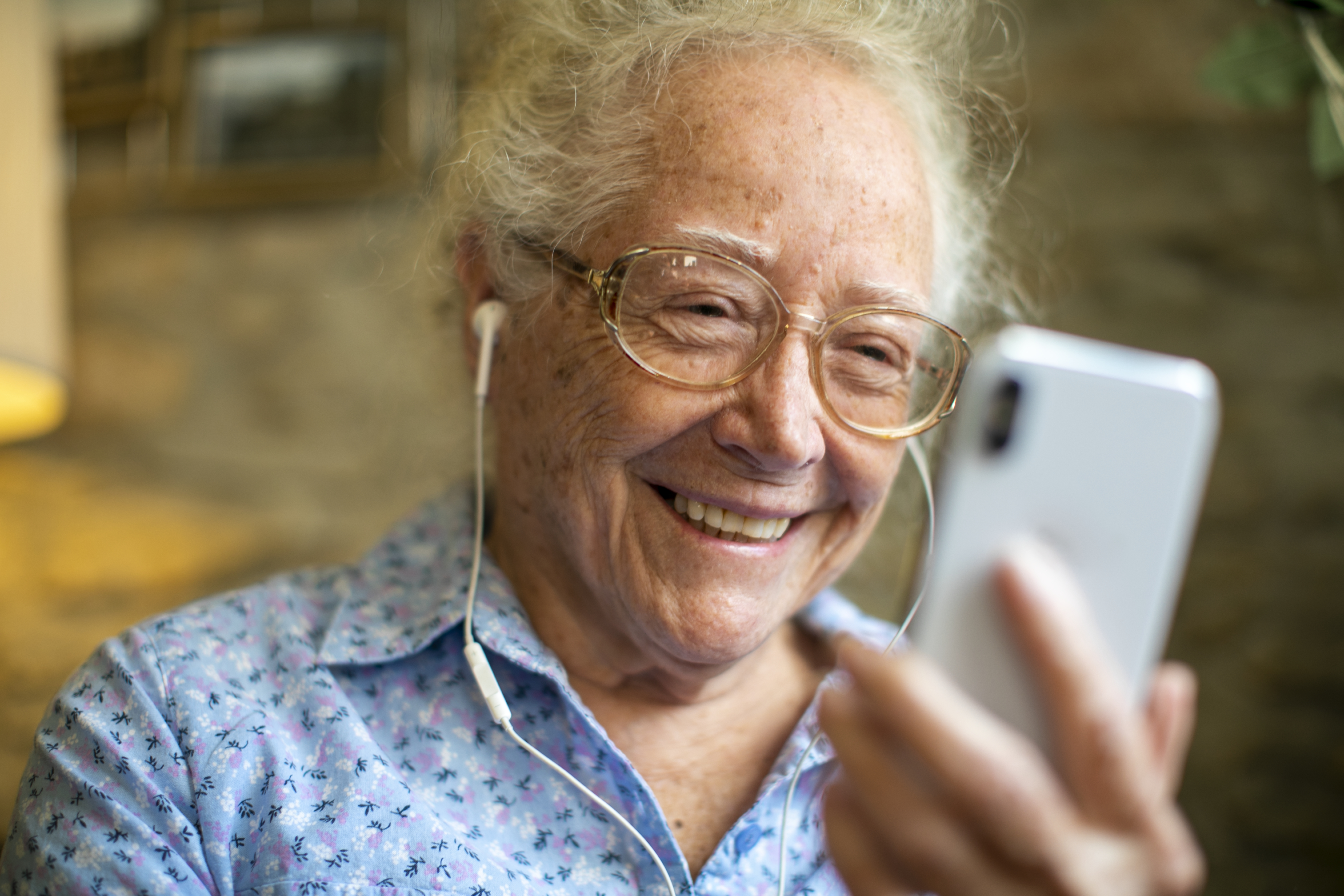 cheerful senior woman listening to a live concert from her smartphone