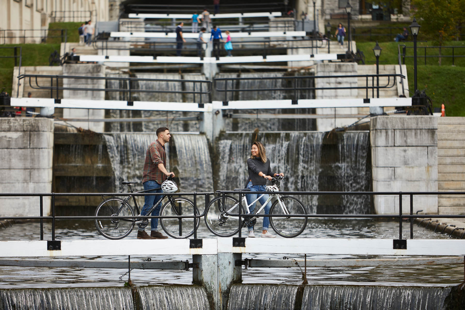 Couple cycling in front of the Rideau Canal Locks