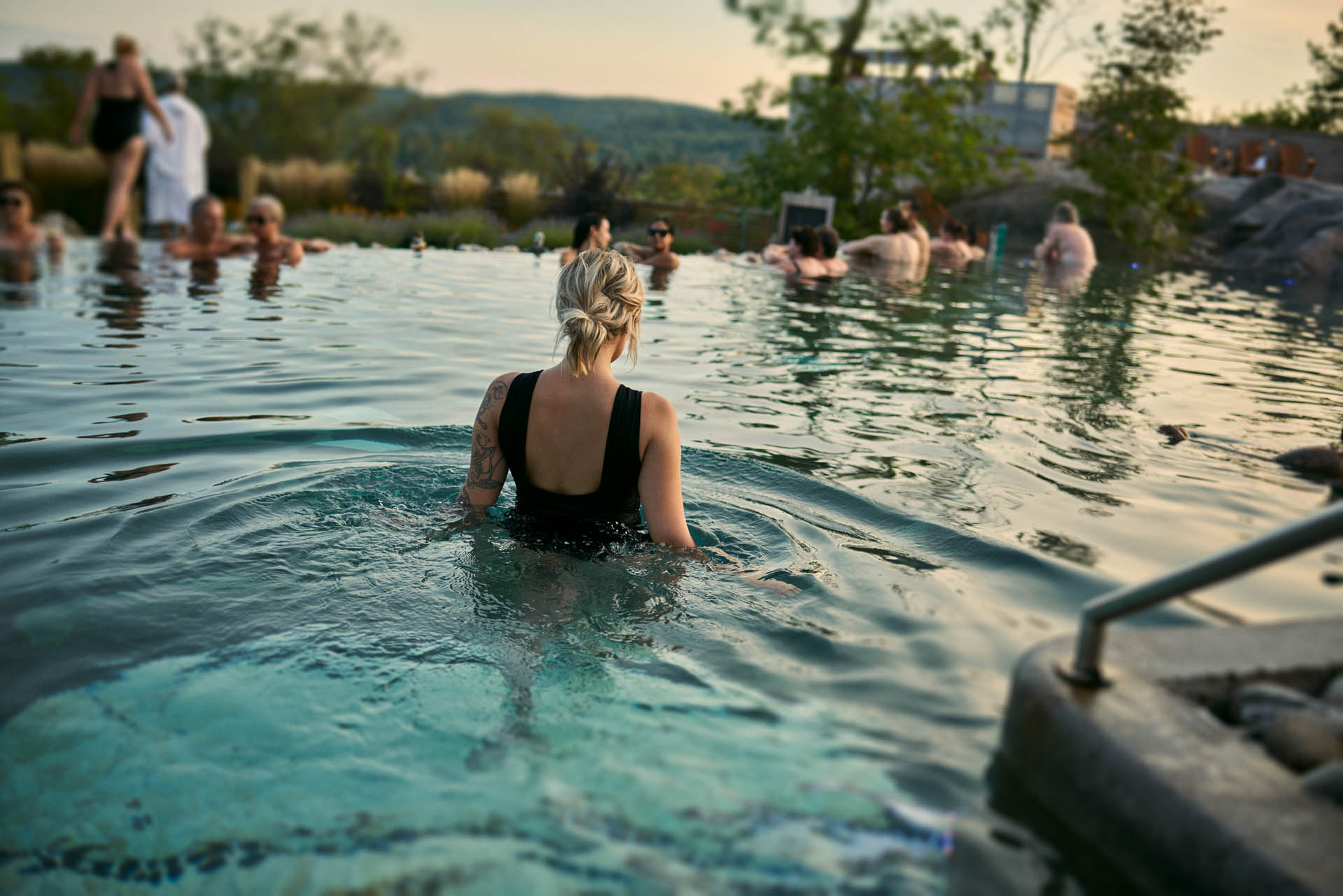 Woman bathing in the infinite pool with others in the background at Nordik Spa Nature