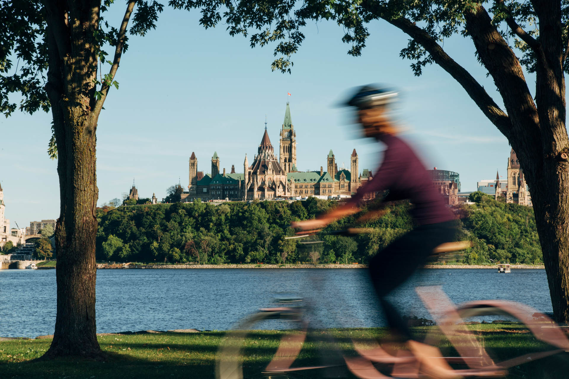 Blurred woman cycling across the Ottawa River with the Parliamant Hill in the background