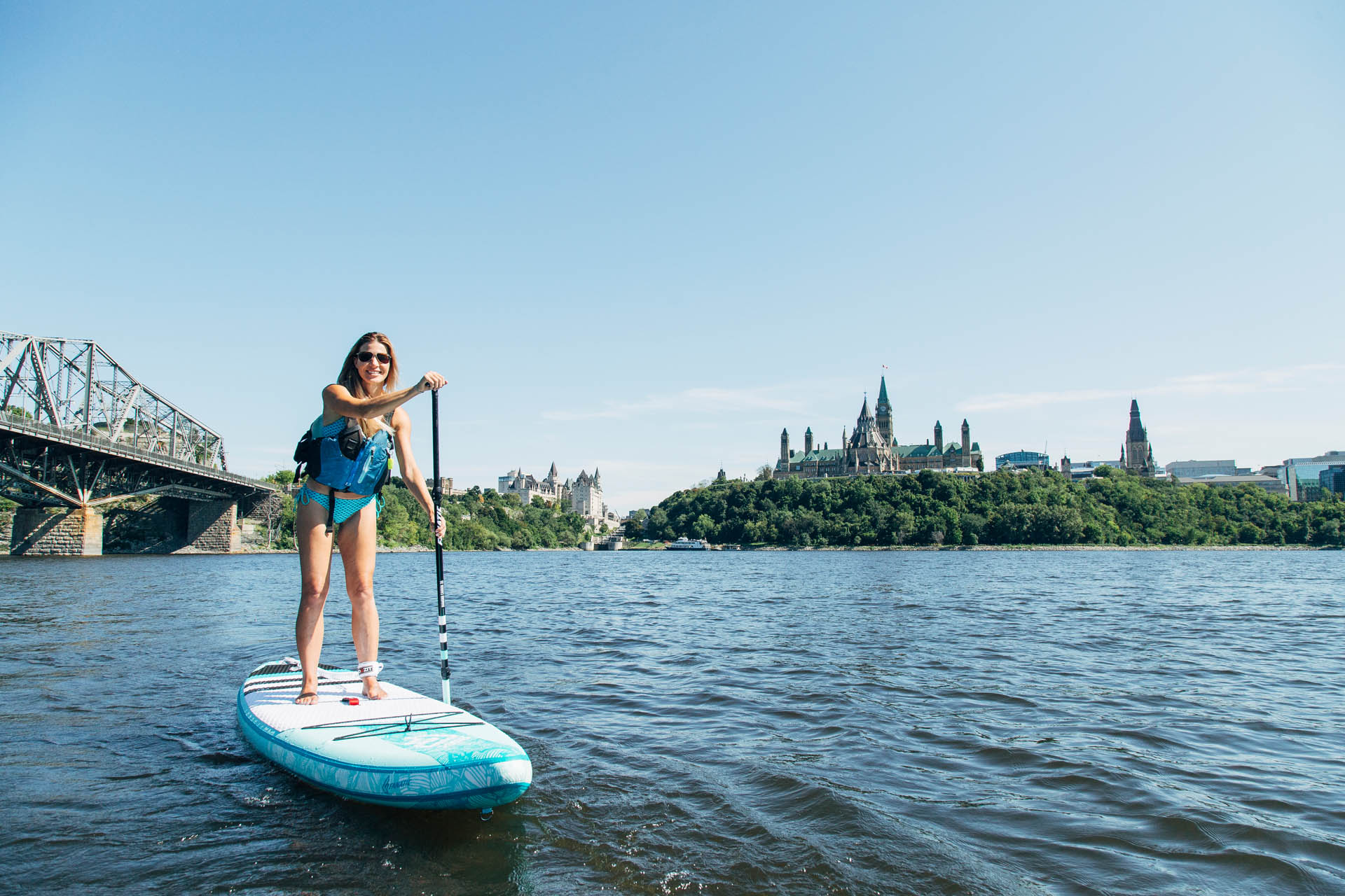 Woman on a stand up paddle board on the Ottawa River in front of Canada's Parliamant