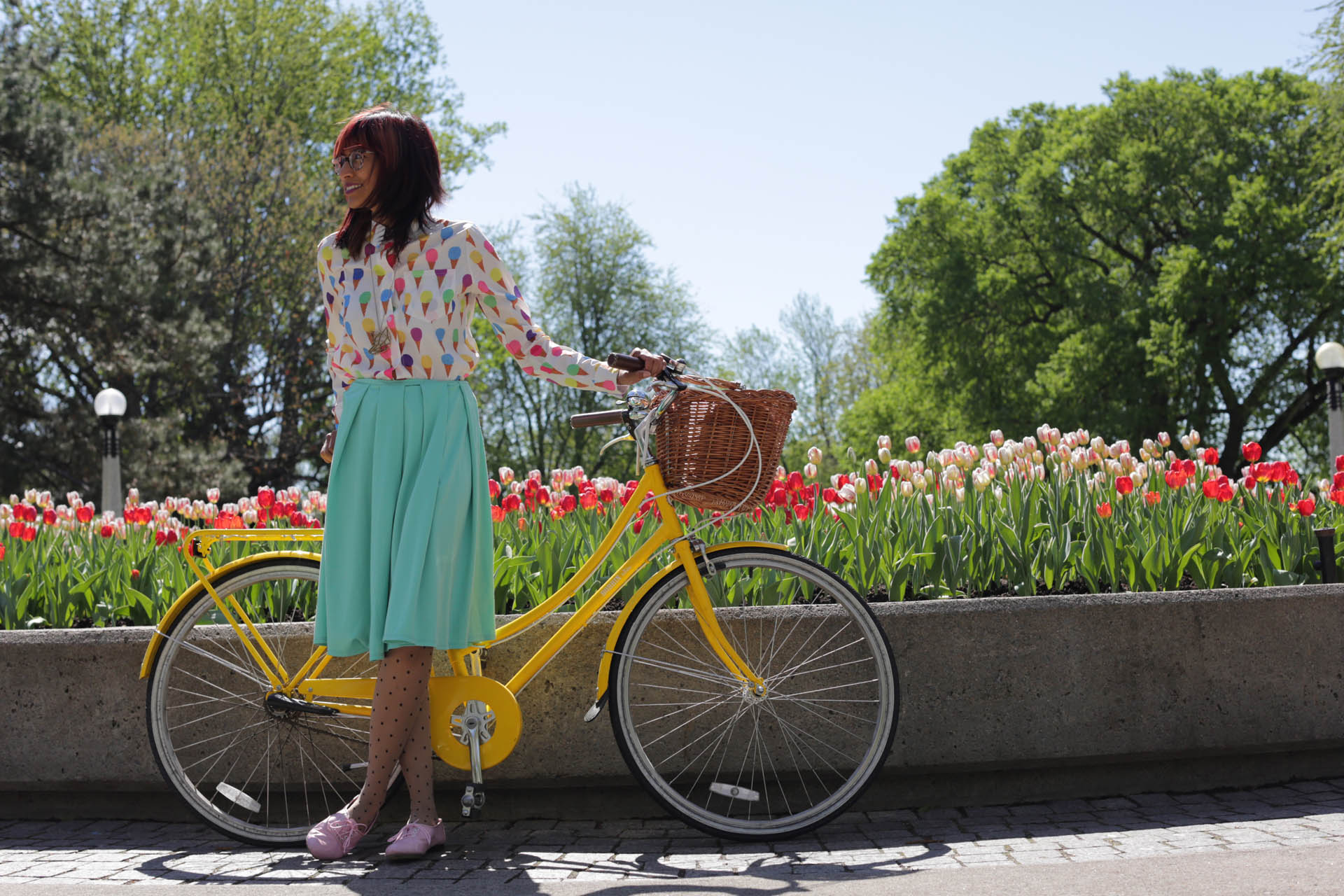 Woman with a bicycle in front of tulips during Canadian Tulip Festival in Ottawa