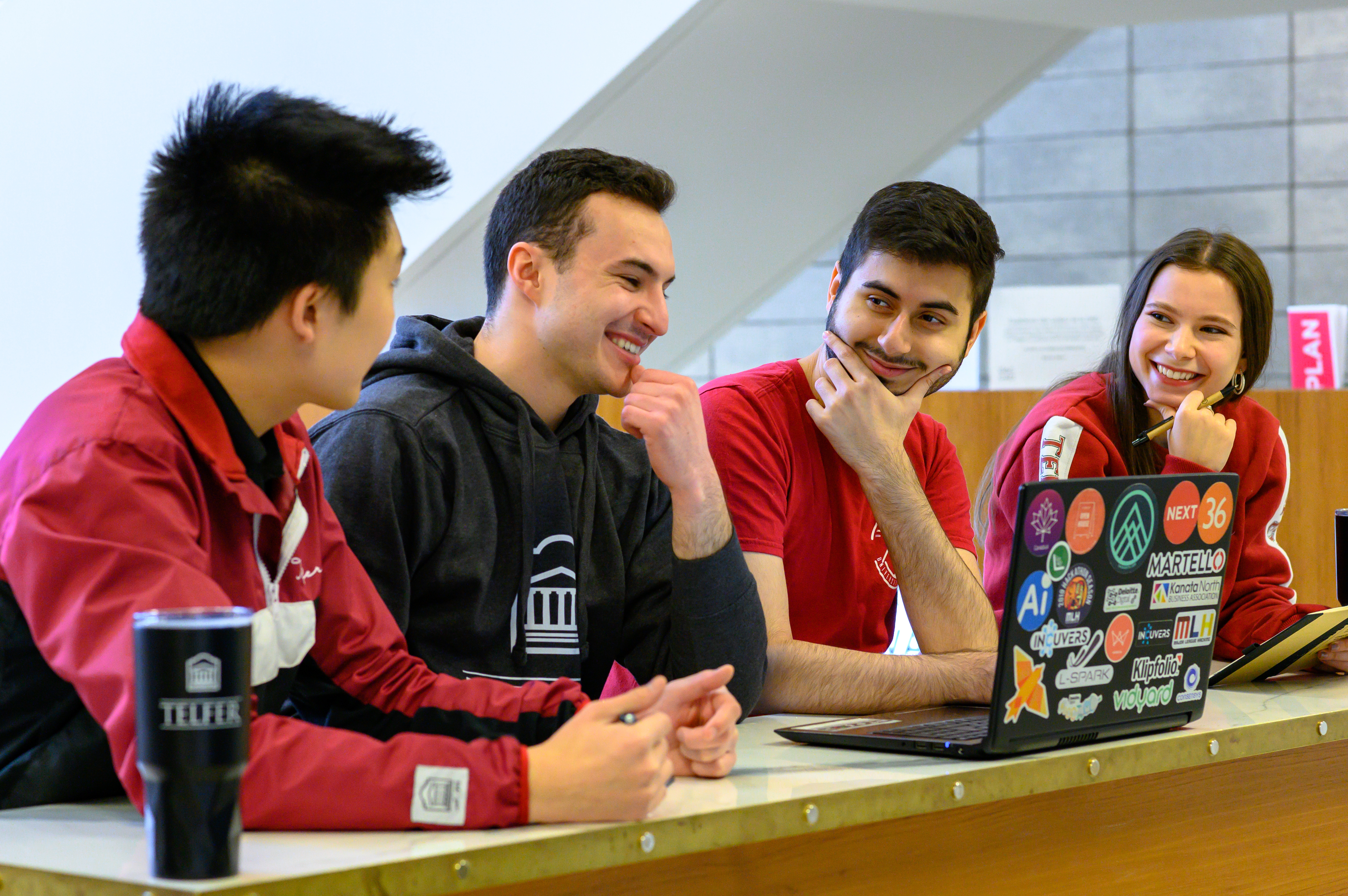 4 Telfer students smiling at one another taking a break from studying while sitting at a desk