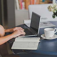 Woman hands working on a laptop with notebook and coffee
