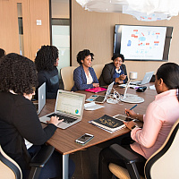 A group of women entrepreneur working and discussing around a conference table