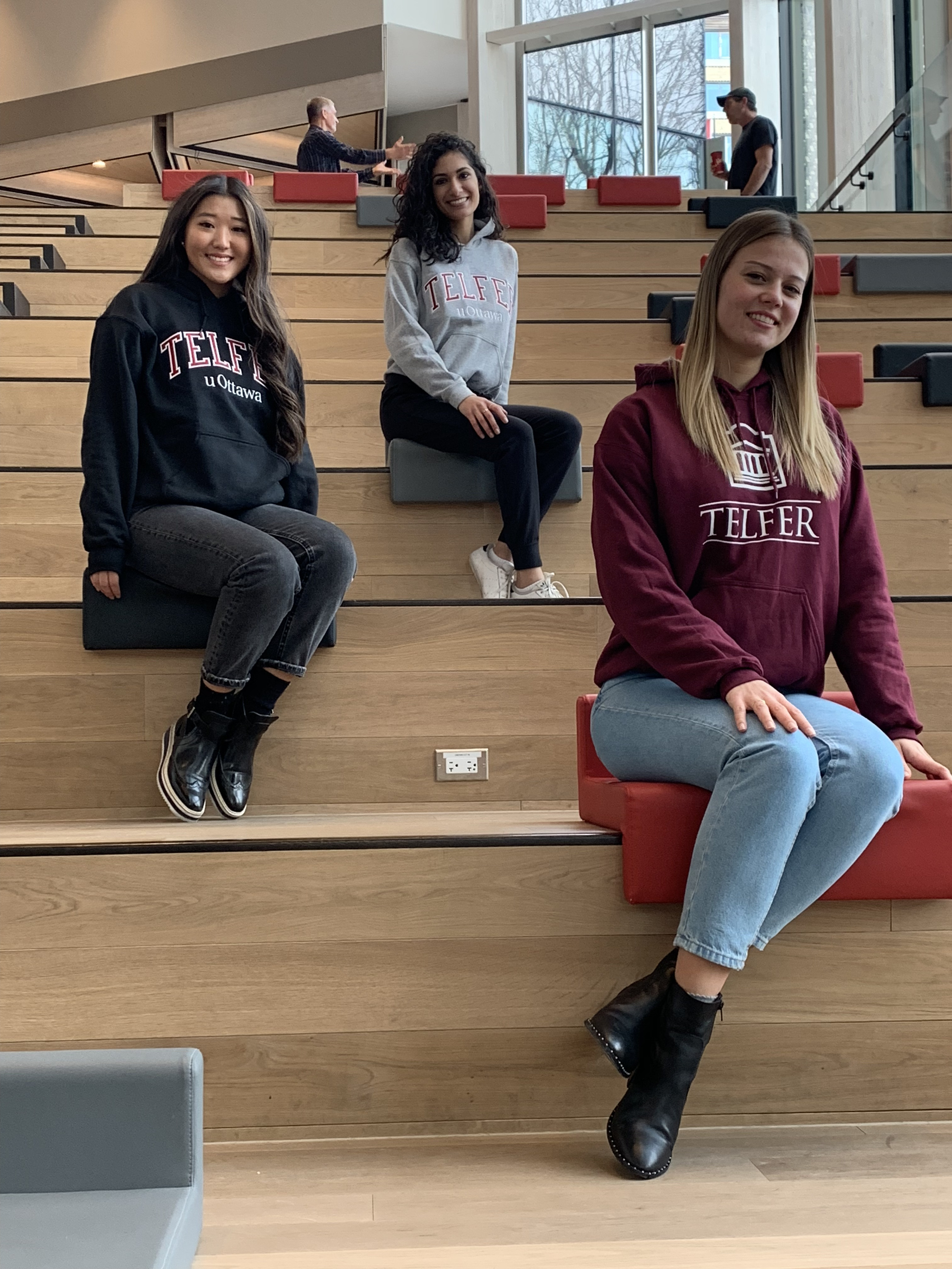 three Telfer students sitting on stairs smiling, wearing Telfer apparel