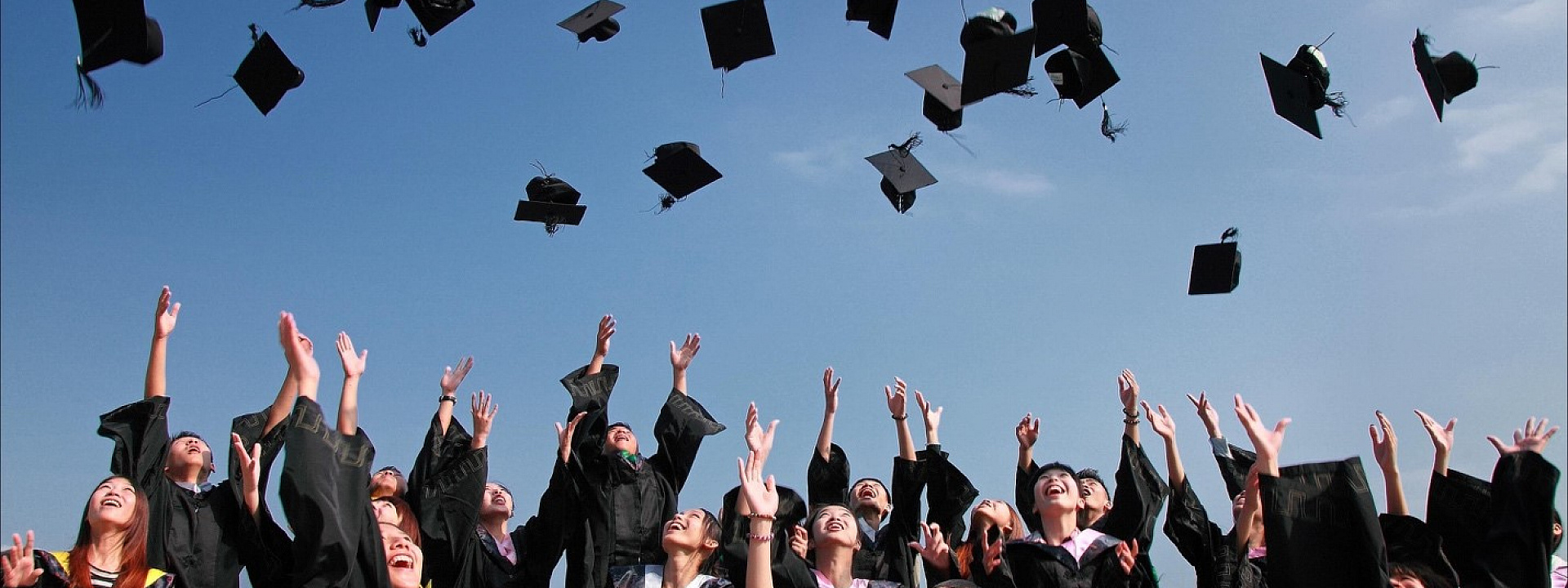 Students throwing their graduate caps into the air on a summer day