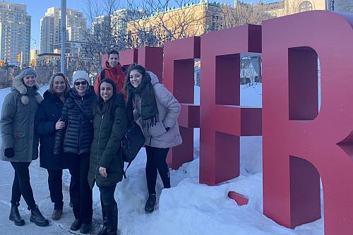 People smiling in front of outdoor Telfer letters