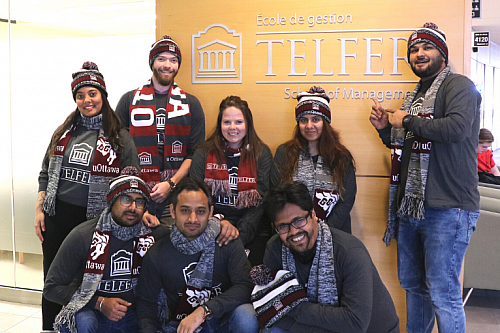 mba games team in front of telfer school of management sign in desmarais building