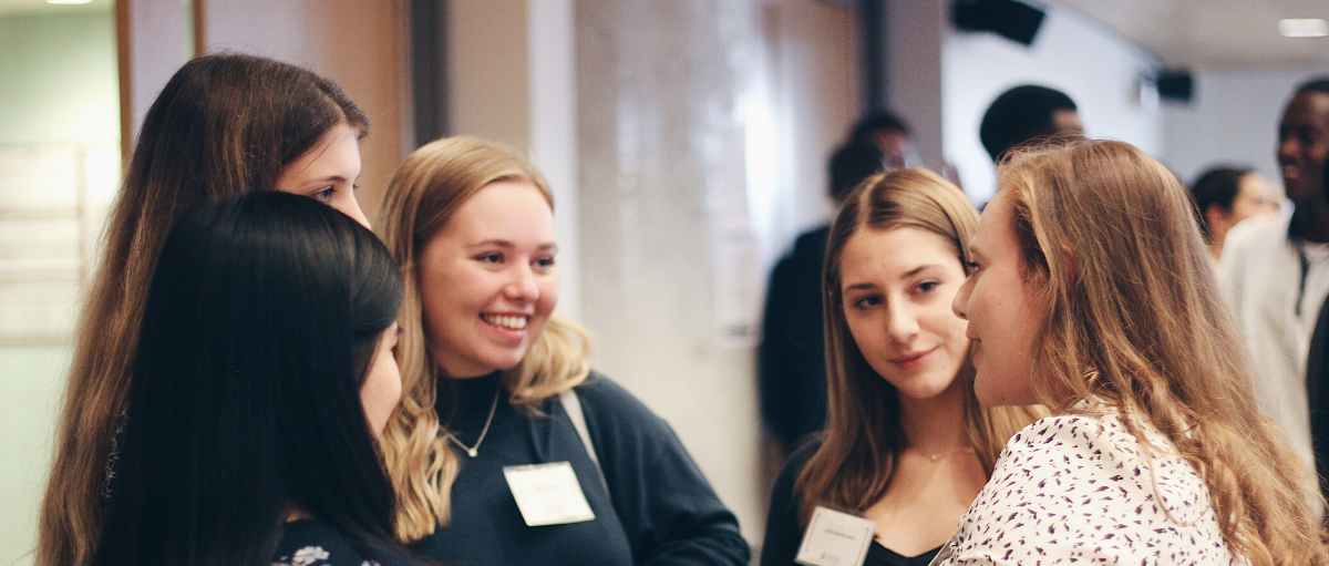 quatre étudiants parlent et sourient lors d'un événement de réseautage