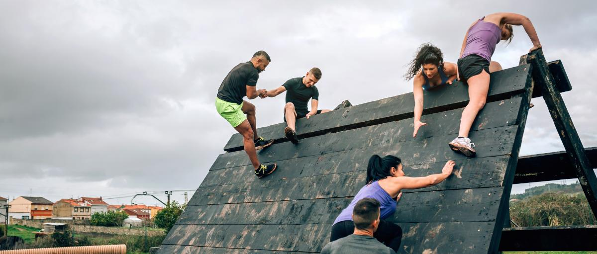 participants in obstacle course climbing a pyramid